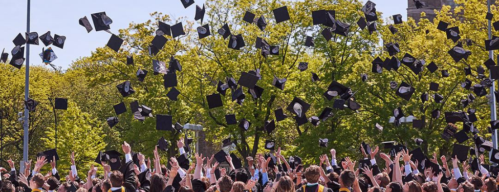 students throwing caps into air on graduation day